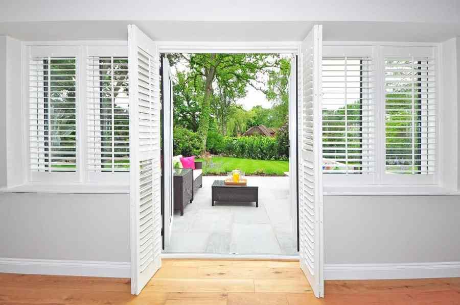 Imagem de porta e janelas com persiana branca aberta.