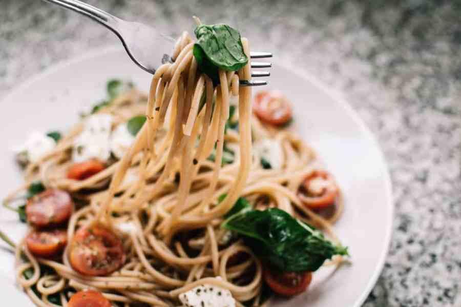 Foto de um garfo retirando macarrão de dentro do prato. A massa é incrementada com queijo, tomate e espinafre.