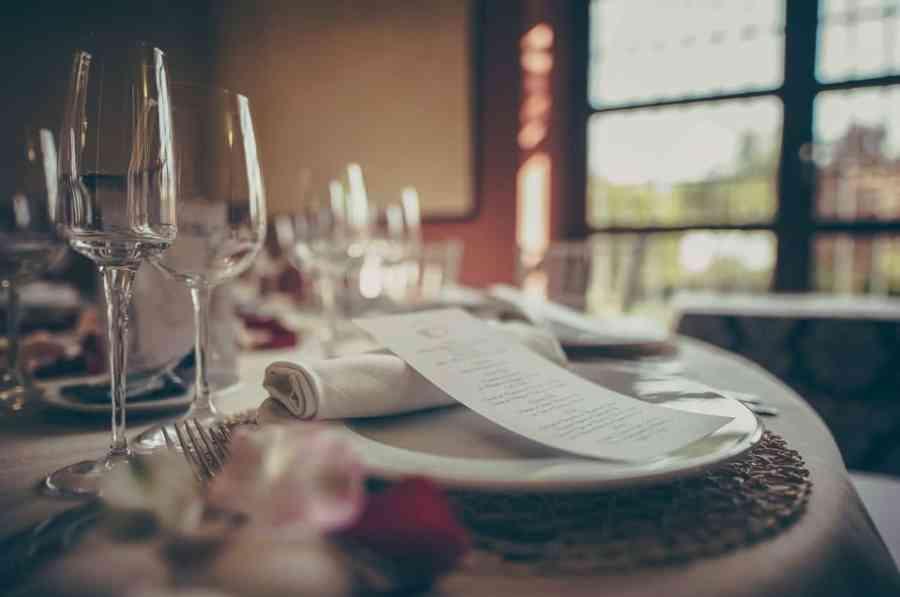 Imagem de mesa de jantar de madeira com jogo de sousplat de madeira sob prato com guardanapo branco e menu.