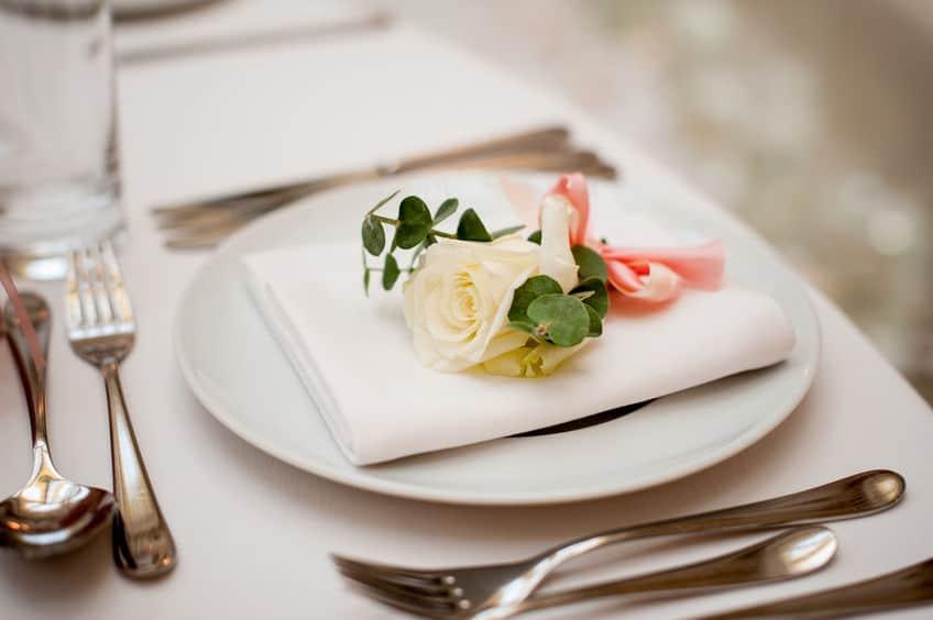 Imagem de prato com guardanapo e flor em cima, talheres e copo ao lado.