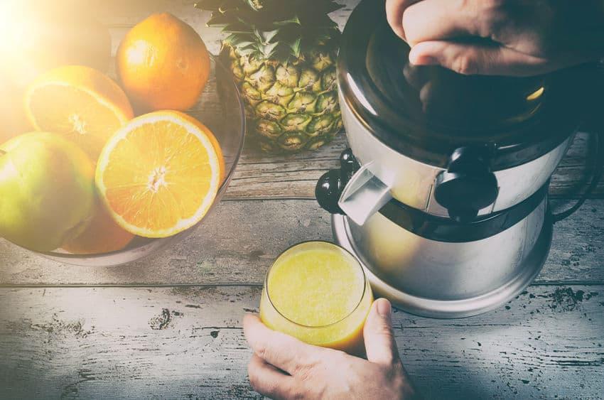 Imagem de uma mão espremendo laranja em um espremedor automático, enquanto outra mão segura um copo cheio de suco, há laranjas cortadas ao lado do espremedor.