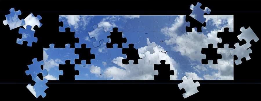 Quebra-cabeça com a imagem do céu azul com nuvens e algumas peças soltas.