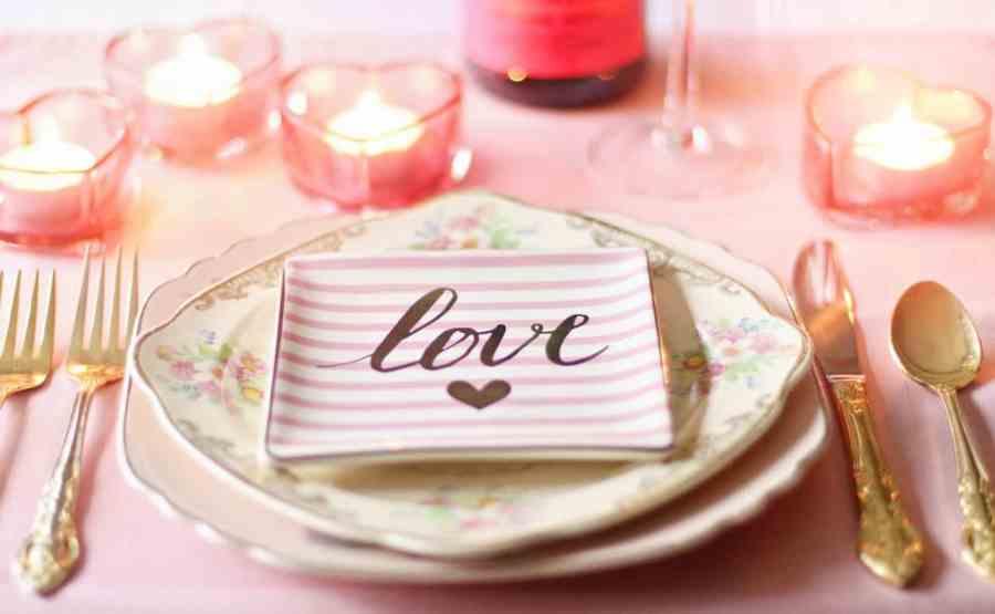 Imagem de mesa de jantar romântica com talheres dourados, velas em formato de coração e prato com tema florido sobre sousplat quadrado.