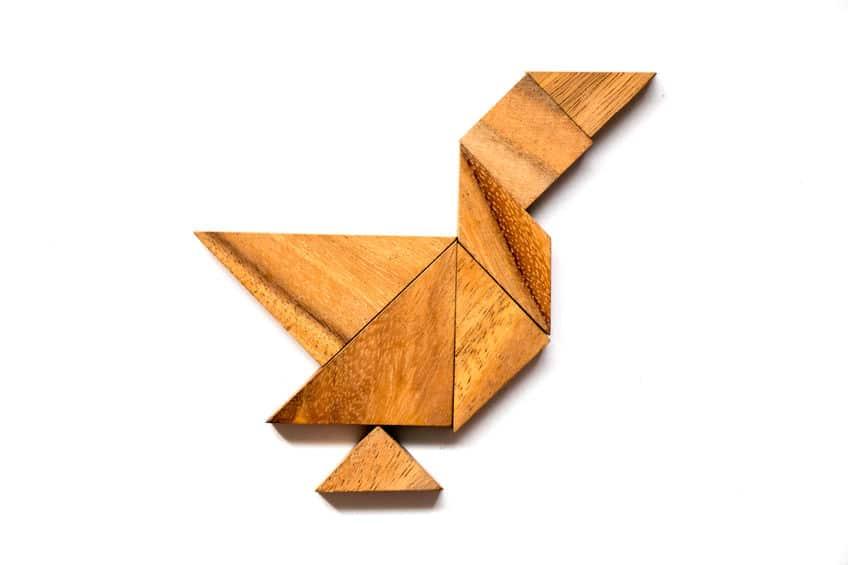 Quebra-cabeça chinês, Tangram, com peças de madeira formando um pássaro.