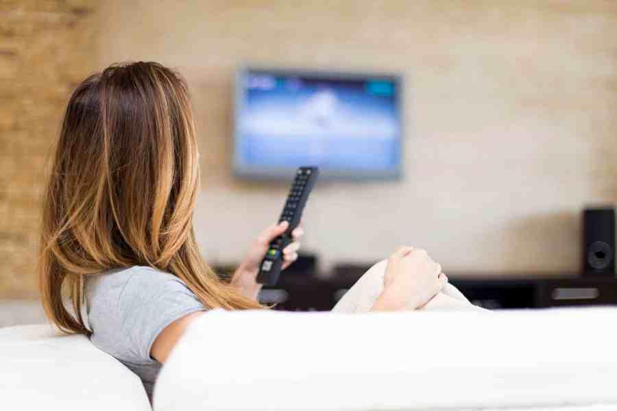 Imagem mostra mulher sentada no sofá vendo tv com controle na mão.