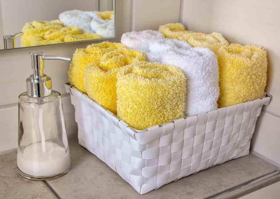 Vidro de sabonete líquido e kit de toalhas coloridas na pia do banheiro.