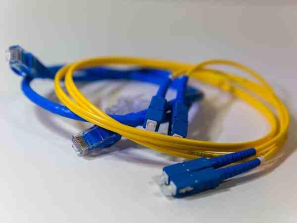 Um cabo óptico amarelo com conectores em azul e branco.