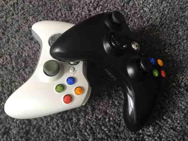 Um controle Xbox 360 preto ao lado de um controle Xbox 360 branco.