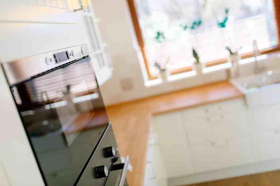 Imagem mostra um forno de embutir em uma cozinha branca.