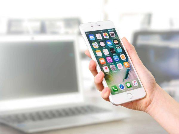 Na foto uma pessoa segurando um iPhone com computadores ao fundo.