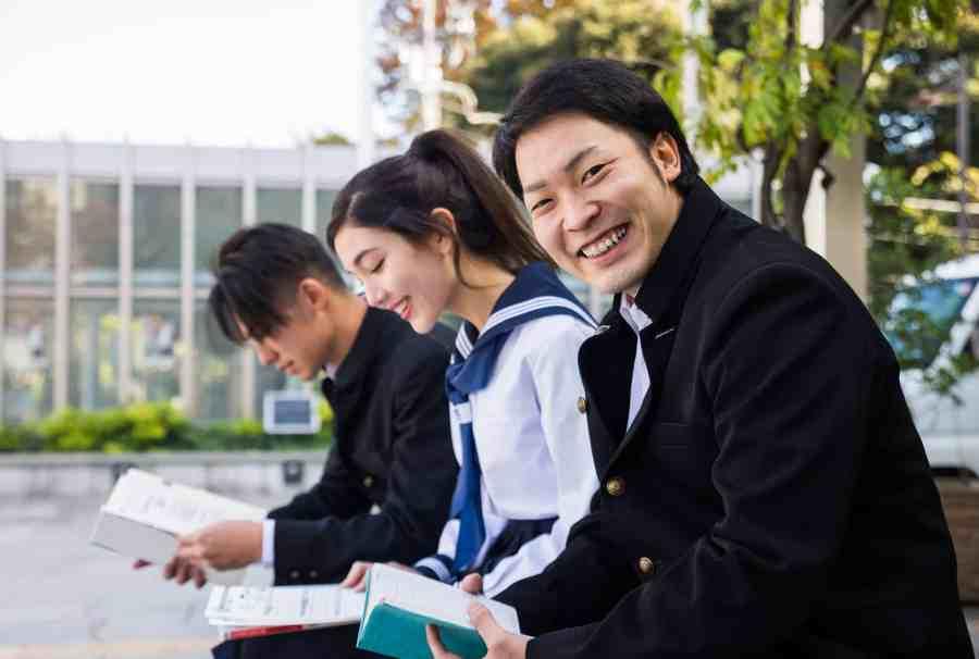 Alunos sentados no pátio da escola lendo mangás.
