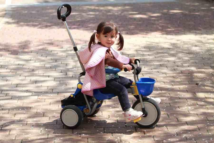 Menina no triciclo infantil com haste de controle na traseira.