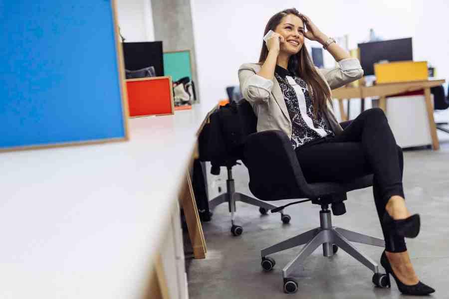 Imagem de mulher sentada em cadeira de escritório.