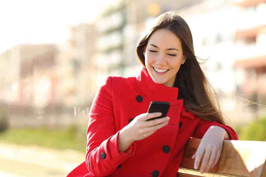 Imagem de mulher sentada em banco mexendo no celular.