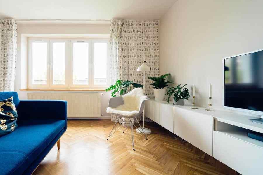 Na foto uma sala de estar com um sofá azul e móveis brancos com plantas no canto e uma televisão em frente a uma janela.