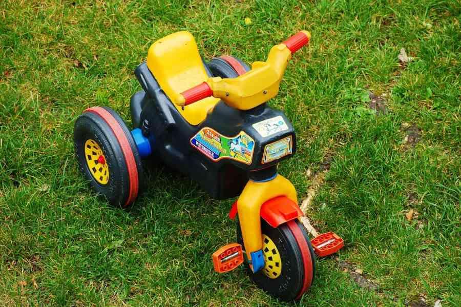 Triciclo infantil de plástico, colorido sobre grama.