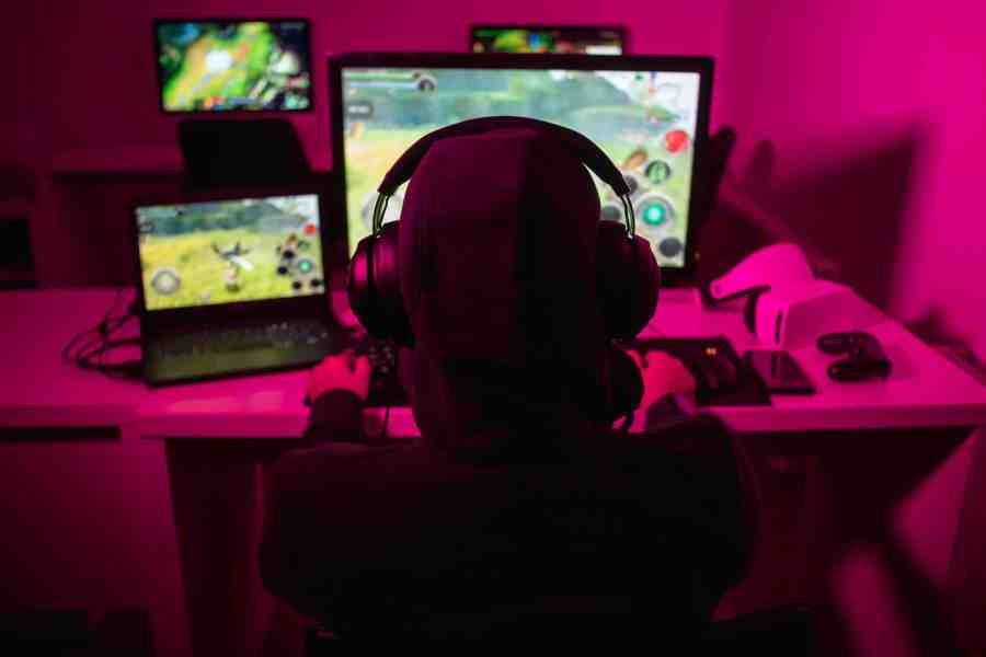 Uma criança em um quarto joga um jogo de computador. Ao lado da tela do PC existe um notebook aberto com outro game.