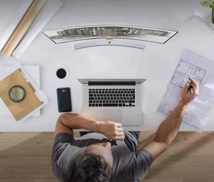 Imagem de um homem navegando em um computador com monitor curvo.