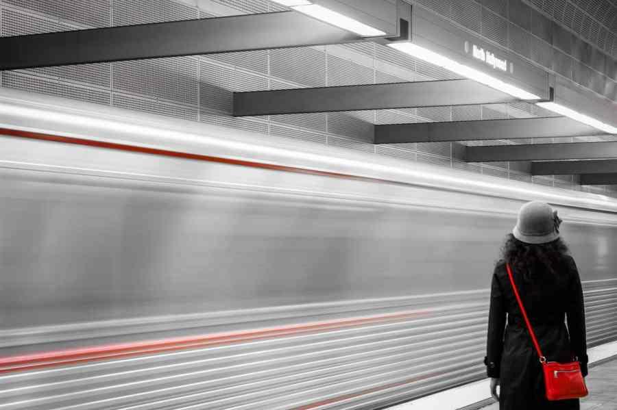 Foto em preto e branco com detalhes em vermelho, de uma mulher parada em uma estação de metrô, com um metrô em movimento a sua frente. Ela usa chapéu e bolsa transversal.