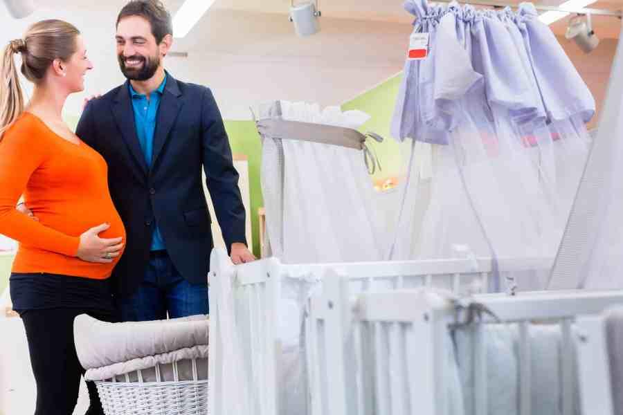 Na foto um casal grávido olhando berços.