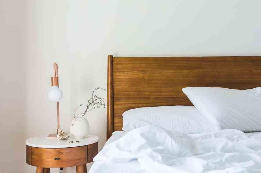 Na foto uma cama com cabeceira de madeira e um criado-mudo de madeira com tampo branco com uma luminária e um vaso com flores em cima.