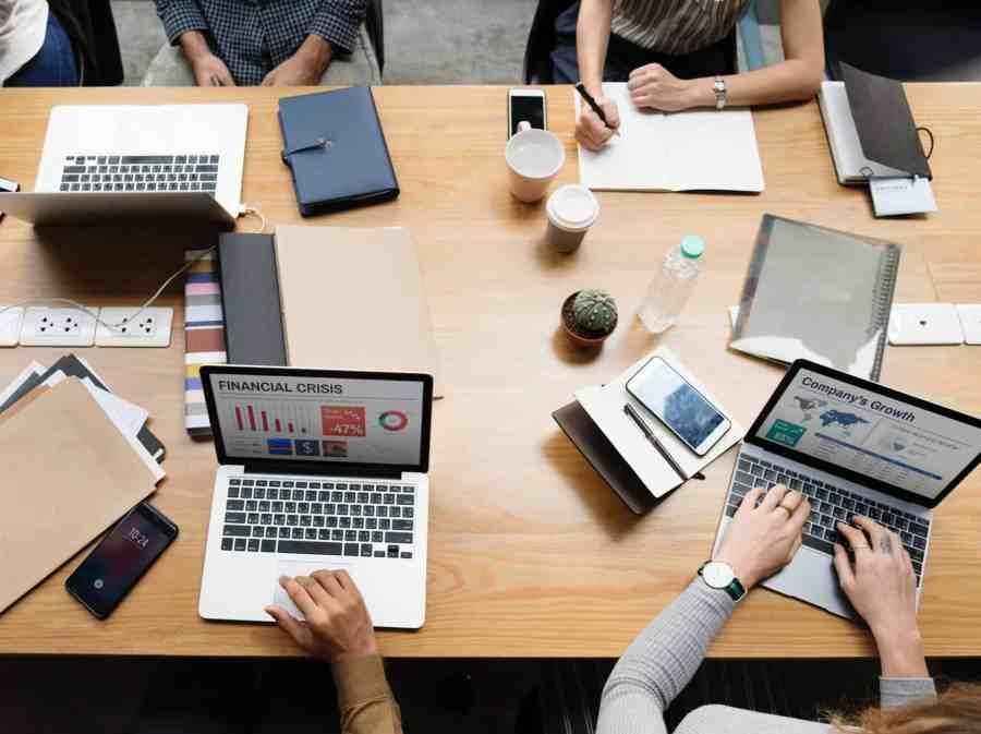 Pessoas em mesa usando notebooks.