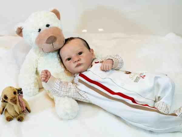 Imagem de um boneco reborn com um urso de pelúcia.