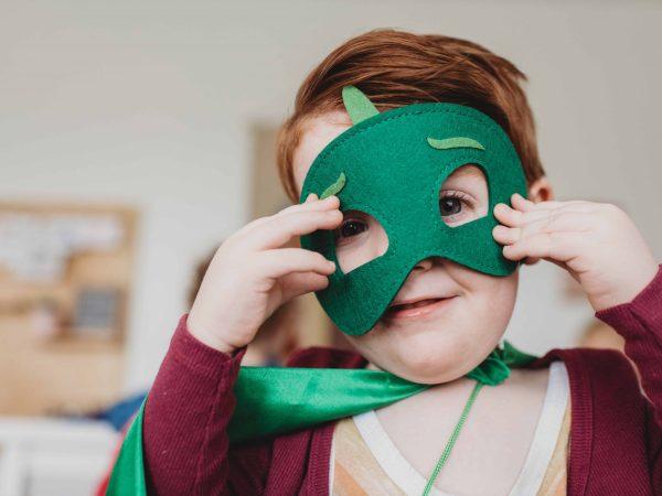 Na foto um menino usando uma máscara do Lagartixo do desenho PJ Masks.
