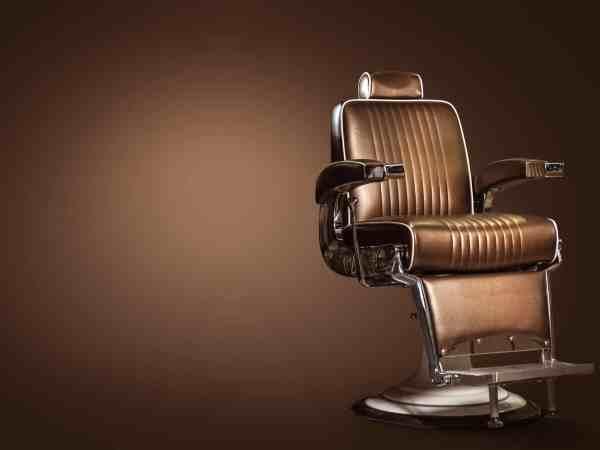 Cadeira de barbeiro em couro marrom.