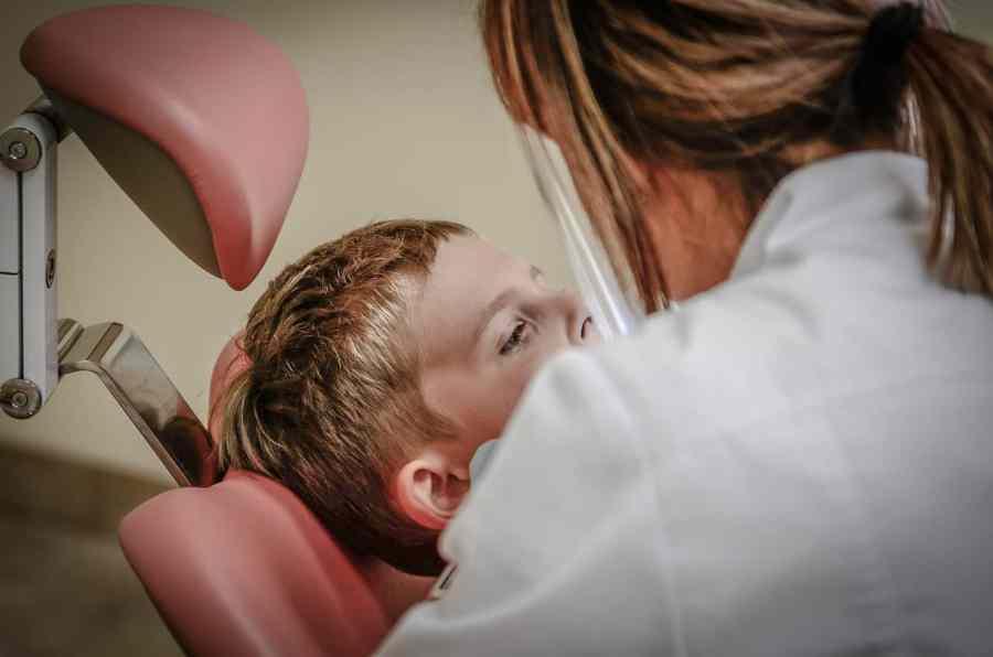 Na foto uma odontologista tratando um menino.