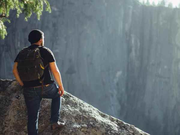 Um homem chegando na ponta de uma montanha observando uma montanha maior na frente em um ambiente natural montanhoso.