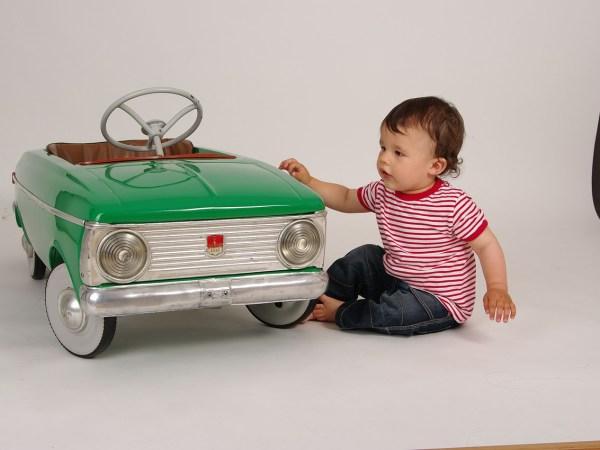 Imagem de uma criança ao lado de um carro infantil.