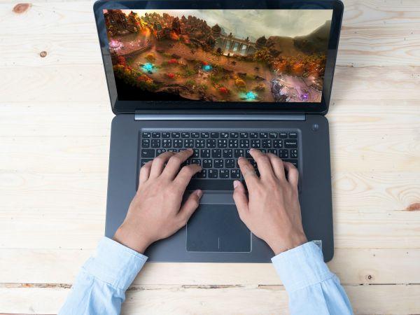 Mãos teclando em notebook gamer.