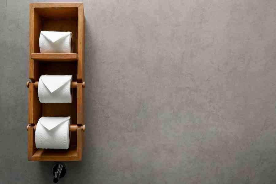 Imagem de um porta rolos de madeira com três rolos de papel higiênico.