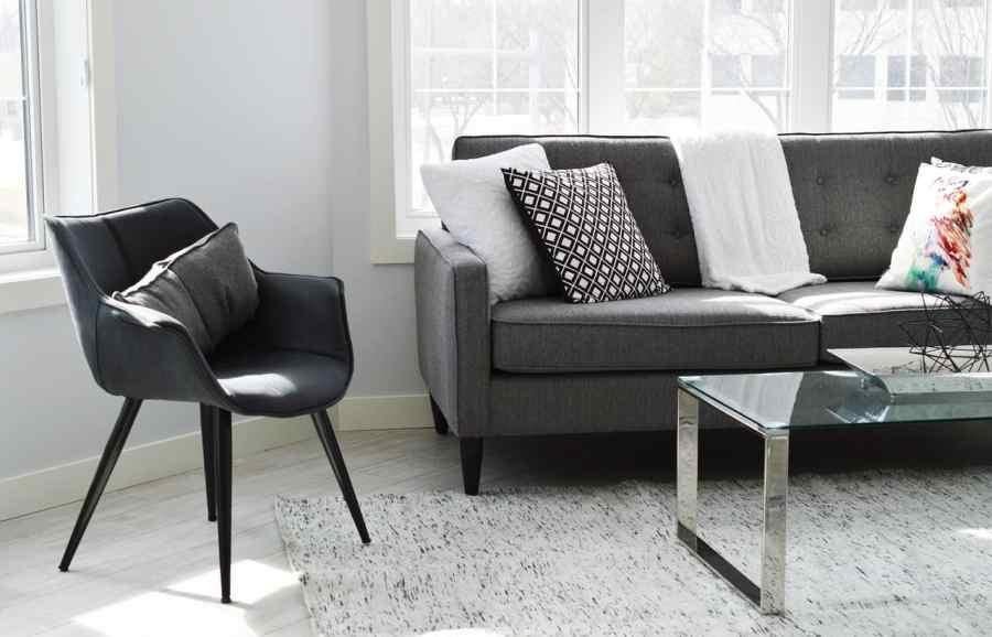 Na foto um sofá cinza com almofadas e uma manta ao lado de uma poltrona na cor preta e uma mesa de centro em vidro.
