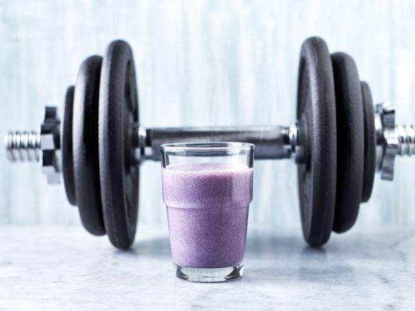 Copo de vitamina com haltere de musculação.