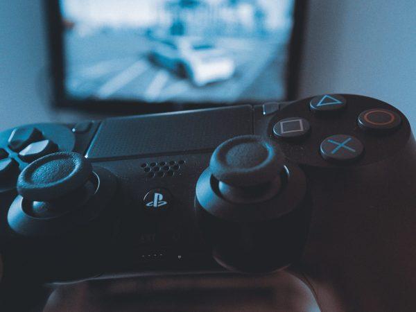 Imagem de pessoa jogando um jogo de corrida no Playstation 4 com controle DualShock