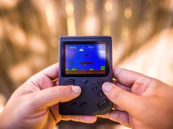 Imagem mostra duas mãos jogando o game Mario num console portátil.