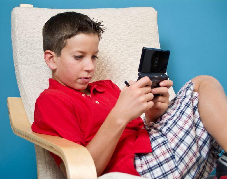 Niño jugando en sofá con Nintendo portatil