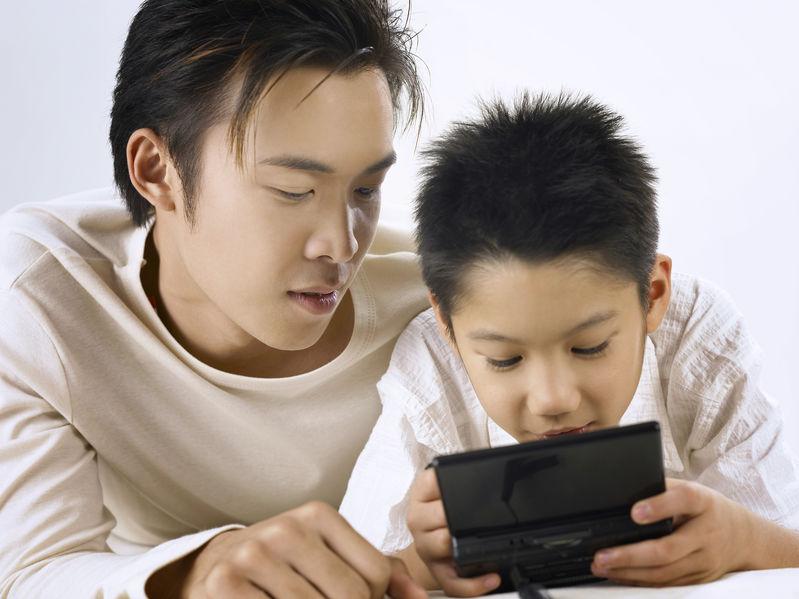 Padre e hijo con videojuego portátil