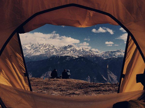 """Imagem mostra, a partir de uma """"moldura"""" formada por uma barraca, uma família sentada no topo de um monte, observando a paisagem montanhosa."""