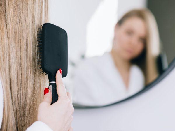 Mulher loira penteia seus cabelos longos com uma escova raquete preta em frente a um espelho