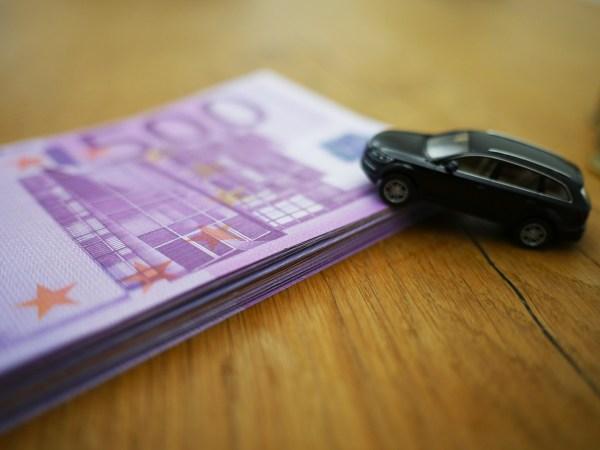 Notas de dinheiro e carro em miniatura.