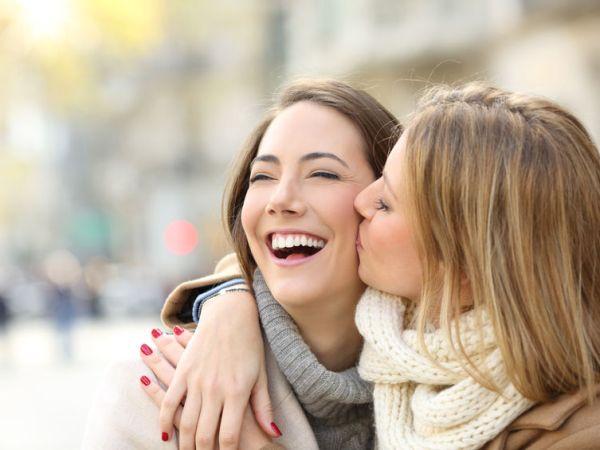 Na foto uma mulher dando um beijo na bochecha de outra.