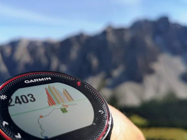 Imagem de um relógio Garmin no pulso com montanhas e céu azul de fundo