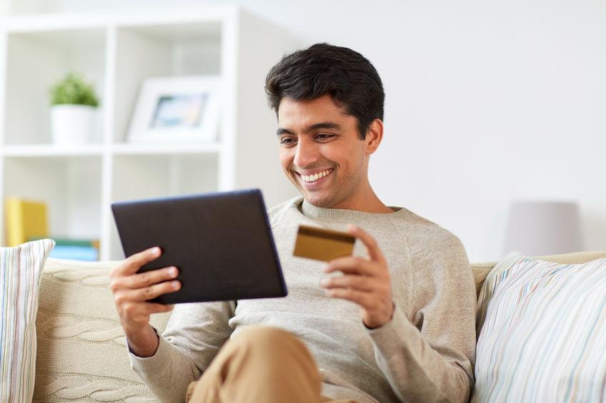 Homem sentado no sofá mexendo em um tablete com cartão de banco na mão.
