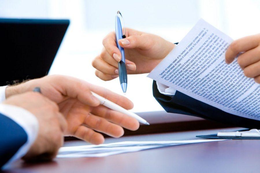 Homem segurando caneta e contrato.