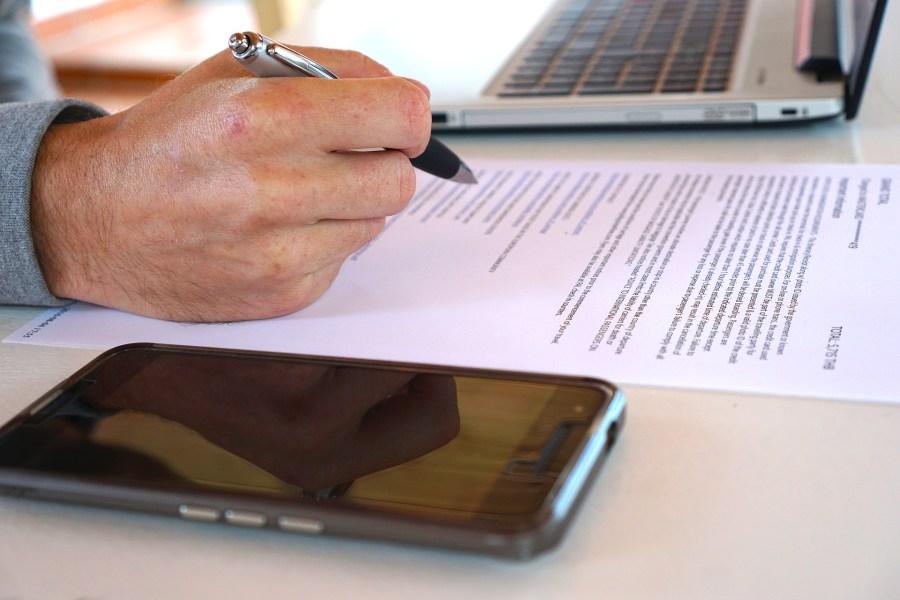 Mão masculina segurando caneta e analisando contrato entre notebook e smartphone.