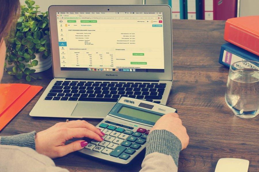Mulher usando calculadora com o notebook aberto na sua frente.