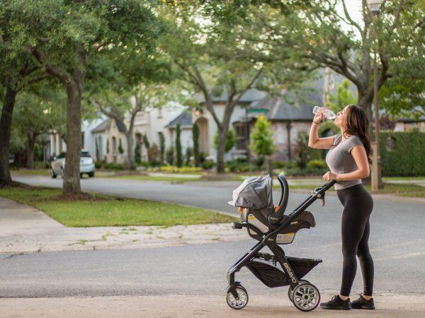 Mãe empurrando carrinho de bebê e bebendo água durante caminhada.
